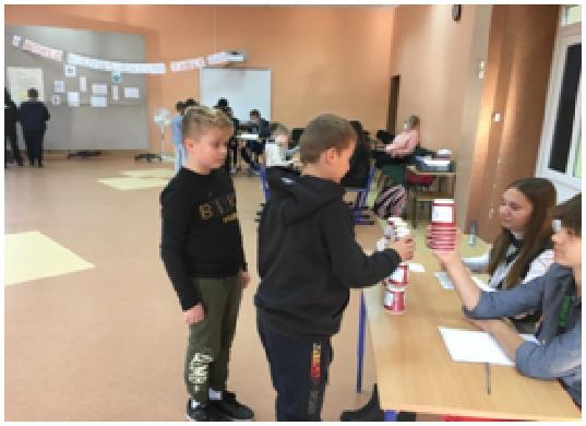 Dwóch uczniów rozwiązuje zadania matematyczne przy stoliku, układając wieżę z kubeczków oznaczonych wynikami mnożenia