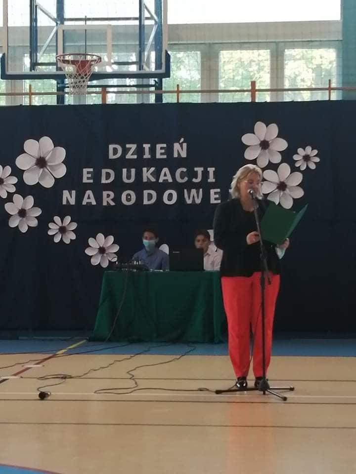 Napis Dzień Edukacji Narodowej w otoczeniu białych kwiatów, osoba stojąca przy mikrofonie