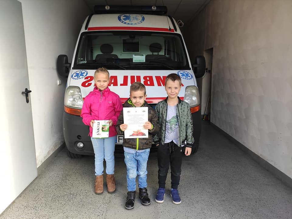 Troje dzieci z laurką - dwóch chłopców i dziewczynka - stoi przed ambulansem
