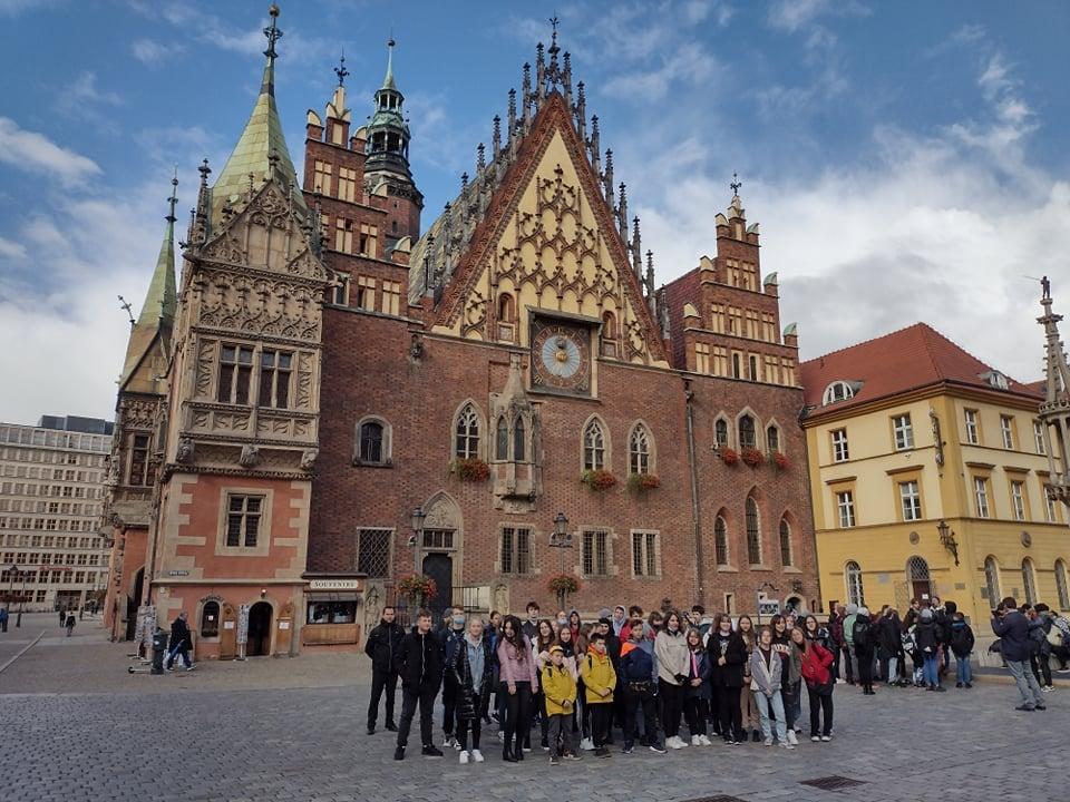 Grupa uczniów wraz z opiekunami , na tle gotyckiego Satrego Ratusza we Wrocławiu
